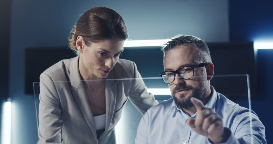 Caucasian businessman and businesswoman sitting in futuristic office and working at glass transparent screen. Place for hologram. Male and female inventors scrolling and tapping like on 3D hologram. Royalty-Free Stock Footage #1052538833