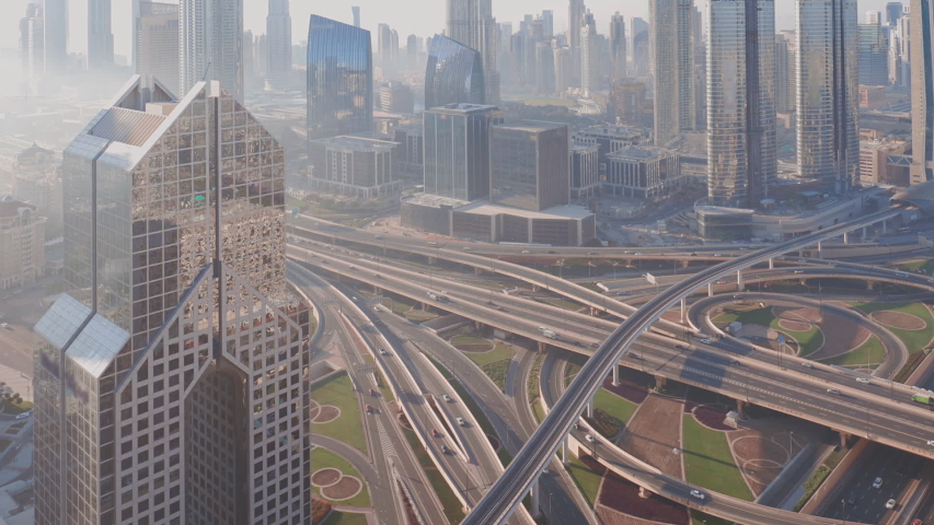 Aerial view of empty highway interchange in Dubai downtown after epidemic lockdown. Cityscapes with disappearing traffic on a bridge and streets. Roads and lanes crossroads without cars, Dubai, United Royalty-Free Stock Footage #1052541677