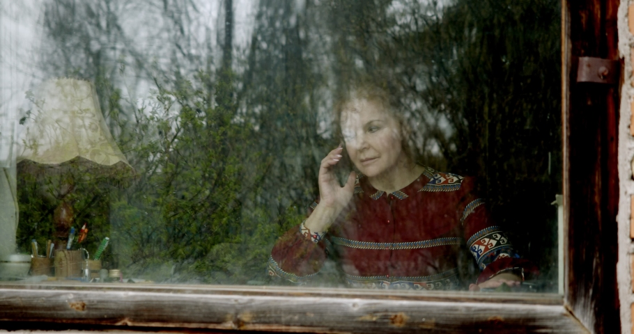 the woman outside the window listens to bad news on her cell phone, takes a deep breath, and is sad in isolation.