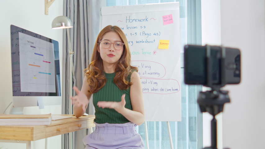 Asian woman, young adult teacher or tutor teaching online on smartphone at home. New normal lifestyle during coronavirus lockdown quarantine. Online remote study, internet education technology concept Royalty-Free Stock Footage #1052545811