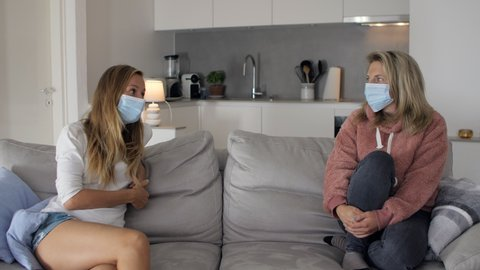 Two friends wearing medical face mask talking on sofa at home. Social distancing with friends and family for safety measures to prevent Covid19 virus to spread.