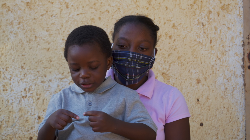 Poverty. Inequality.Young Black African girl puts on a mask on her cute little brother during lockdown to prevent Covid-19 Coronavirus pandemic, South Africa Royalty-Free Stock Footage #1052552015