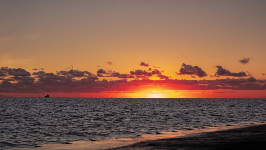 A beautiful panoramic orange and yellow sunrise timelapse over the water of Lake Michigan as the sun rises towards clouds just above the horizon as a flock of geese swim by.