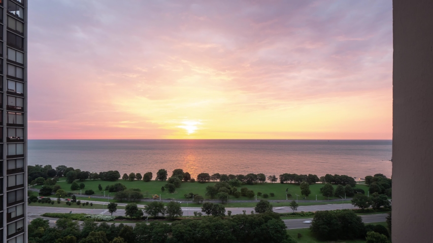 Incredible panning down aerial timelapse of a yellow pink purple and blue sunrise reflects on the water of Lake Michigan as it rises over the horizon with traffic zooming by on Lake Shore Drive below.