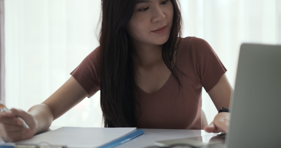 Asian woman working from home with laptop computer self isolation from society to reduce risk, quarantine prevention coronavirus, covid-19 and study e-learning online education technology new normal. Royalty-Free Stock Footage #1052581439