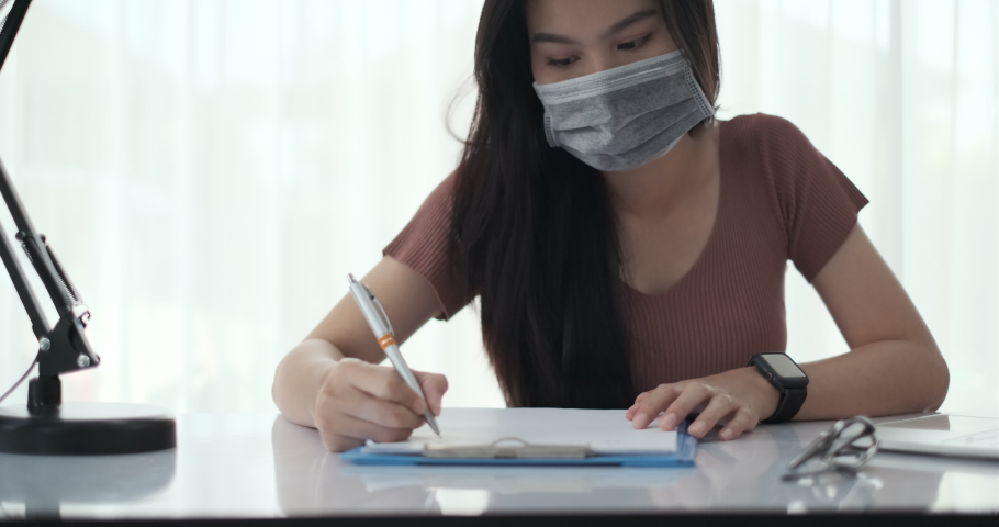 Asian woman working from home with laptop computer self isolation from society to reduce risk, quarantine prevention coronavirus, covid-19 and study e-learning online education technology new normal. Royalty-Free Stock Footage #1052581451