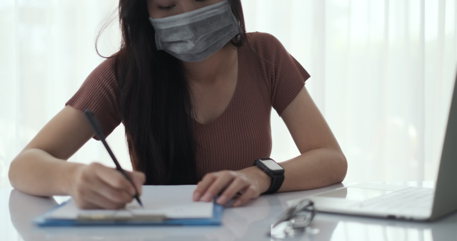 Asian woman working from home with laptop computer self isolation from society to reduce risk, quarantine prevention coronavirus, covid-19 and study e-learning online education technology new normal. Royalty-Free Stock Footage #1052581457