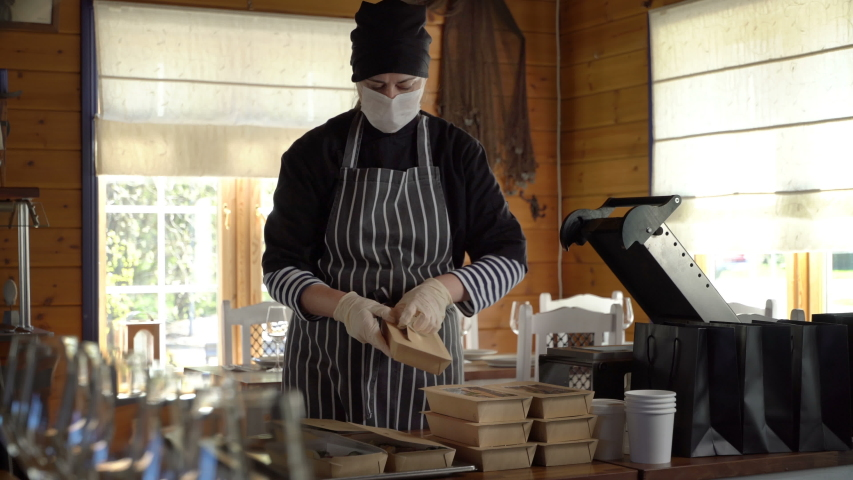 Restaurant worker wearing medical mask and gloves collecting a food box take away. Food delivery services during coronavirus pandemic and social distancing. Online contactless food shopping. Royalty-Free Stock Footage #1052582831