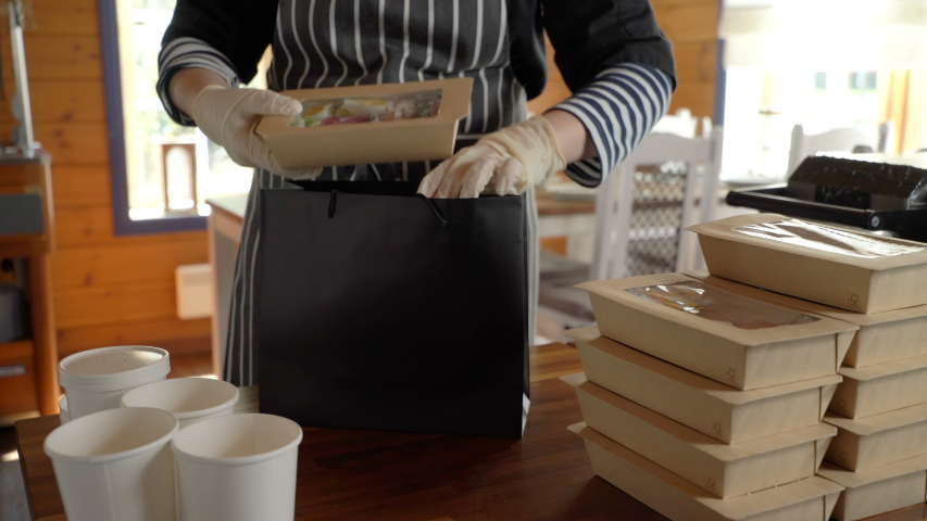 Restaurant worker wearing medical mask and gloves collecting a food box take away. Food delivery services during coronavirus pandemic and social distancing. Online contactless food shopping. Royalty-Free Stock Footage #1052582876