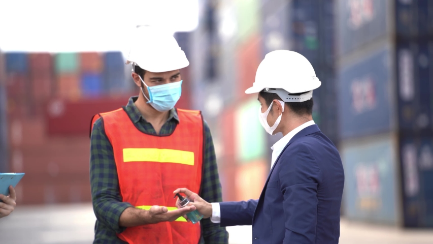 Labor man worker is wearing protection mask face and safety helmet at outdoor warehouse factory. Concept of safety industry worker operating. | Shutterstock HD Video #1052630693