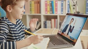 Smart Little Boy Uses Laptop for Video Call with His Teacher. Screen Shows Online Lecture with Teacher Explaining Subject from a Classroom, Boy writes Down Information. E-Education Distance Learning