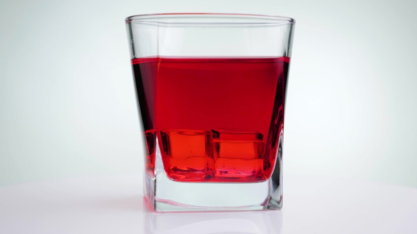 Hand stirs ice cubes with red lemonade using a red straw. Red alcoholic drink in glass rotate on a white background. | Shutterstock HD Video #1052649287