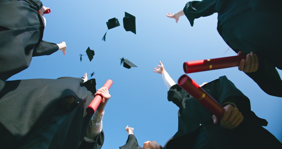 Slow motion of group happy graduates students throw their caps into the air | Shutterstock HD Video #1052667245