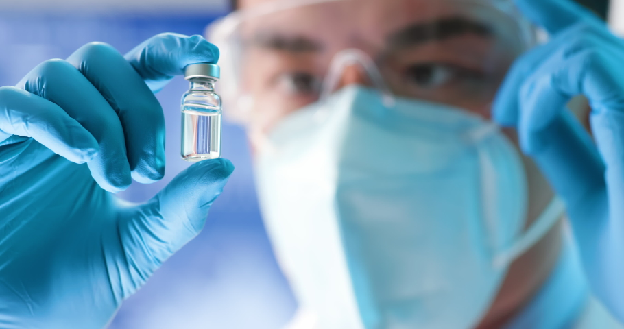 Close up of scientist microbiologist or medical worker look to newest vaccine in the laboratory | Shutterstock HD Video #1052667653
