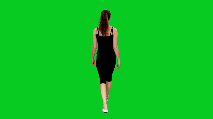 Back view of young attractive slim sporty woman walking against green screen background, chroma key 4k footage