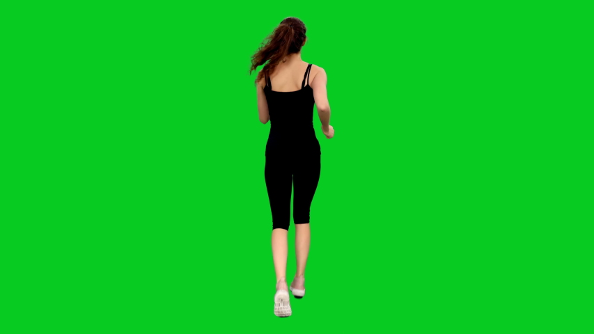Rear view of slim young sporty woman jogging against green screen background, Full body chroma key 4k footage