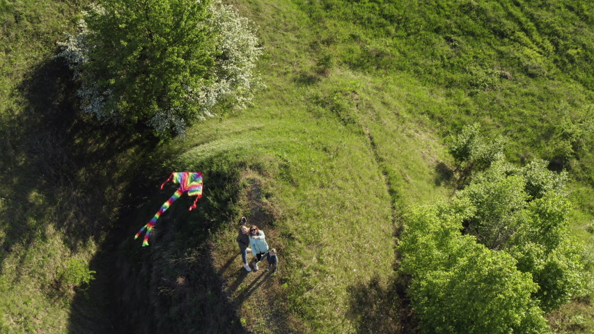 Top view of a young mother with her children plays with a kite on amazing green hilly terrain, aerial view | Shutterstock HD Video #1052678240