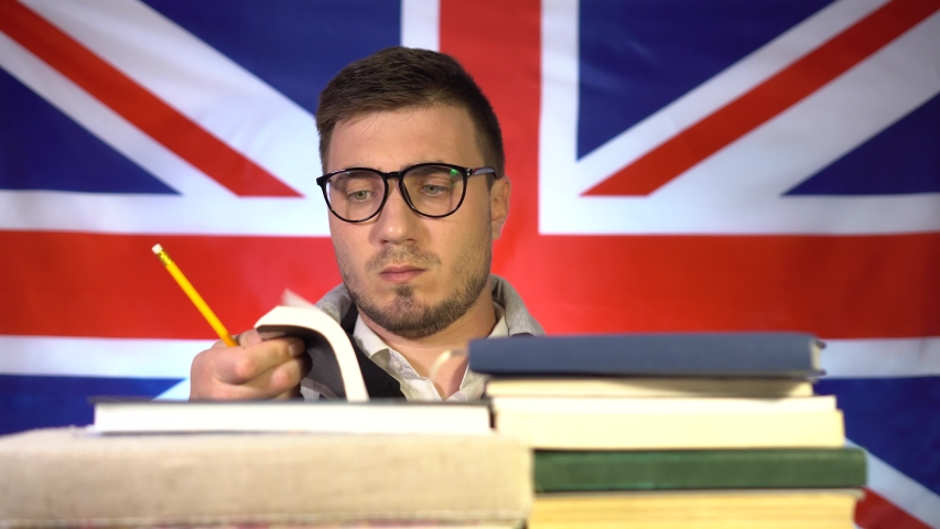 Cute guy student with glasses fluently leafs through a book from a pile of books on the background of the flag of Great Britain. Education in the UK. Education concept.