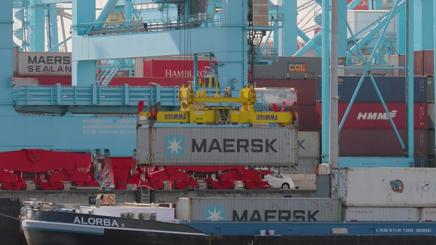 ROTTERDAM, THE NETHERLANDS - SEPTEMBER 18, 2019: Containers loaded onto a ship on automated cranes in the APM Terminals Rotterdam, busiest port of Europe.   Shutterstock HD Video #1052680691