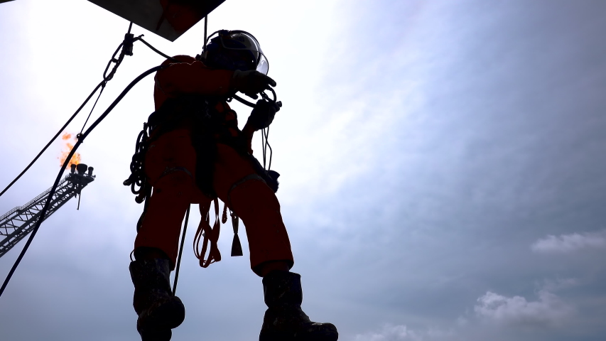 Working at height. Silhouette of abseiler team hanging at the edge oil and gas platform for maintenance works with background flare tip boom burning. | Shutterstock HD Video #1052689676