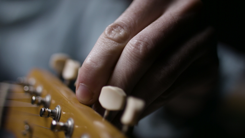 A musician tunes a guitar for a performance. Playing music instrument. Shot on RED camera in 4k. | Shutterstock HD Video #1052695034
