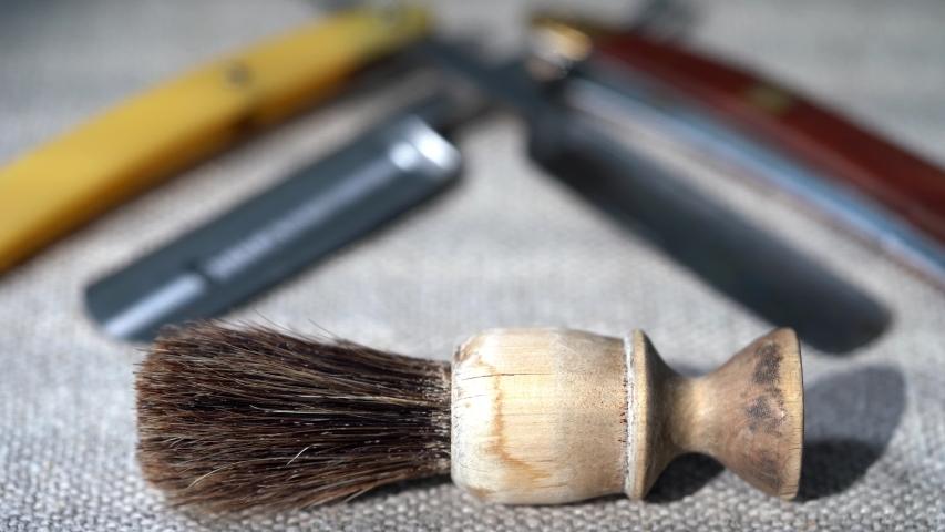 Barbershop. Shaving tools dangerous razor, blades, shaving brush thinning scissors, combs lie on a canvas background. Hairdresser Accessories | Shutterstock HD Video #1052699930