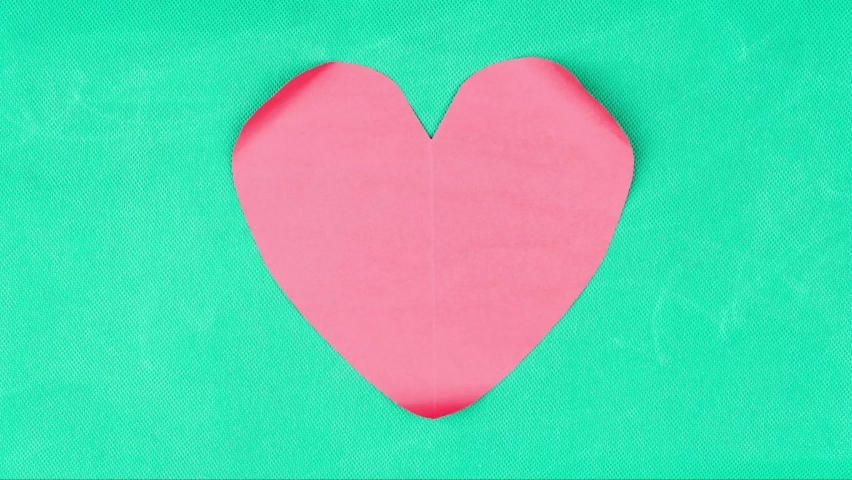 Stop motion of crumpled paper in the shape of a heart on table with loopable seamless background. Shot in 4k resolution