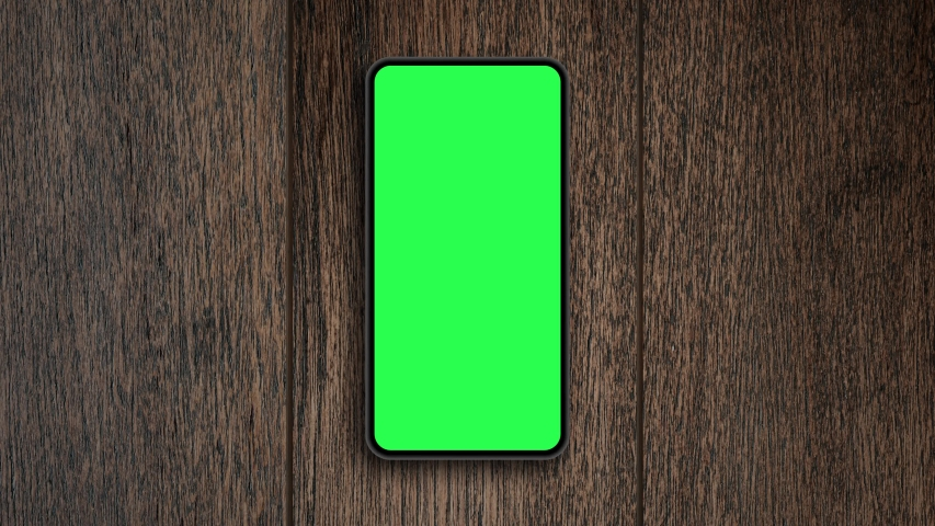 Top view, Smart phone place on table wood with green screen, Close-up the cell phone is on the brown desktop with chroma key, Green screen telephone, slider and top view. | Shutterstock HD Video #1052702675