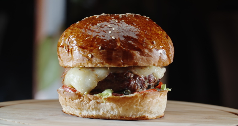 Amazing tasty appetizing burger with various fresh ingredients and buns on wooden board, isolated on black background - unhealthy living, fast food concept close up 4k footage