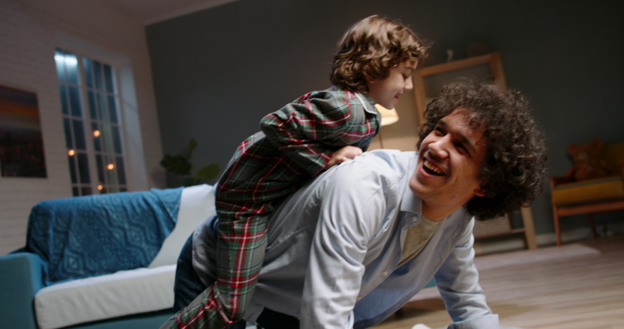 Young asian father playing with his little son. Funny kid with curly hair doing a piggy back ride, having fun at home - happy family, recreational pursuit concept 4k footage | Shutterstock HD Video #1052706740
