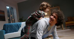 Young asian father playing with his little son. Funny kid with curly hair doing a piggy back ride, having fun at home - happy family, recreational pursuit concept 4k footage