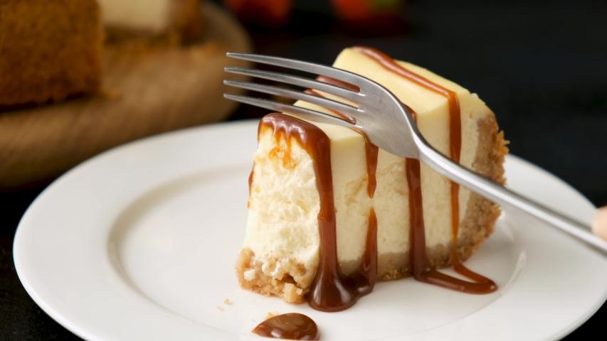 Eating caramel cheesecake. Taking bite of caramel cheesecake with fork Royalty-Free Stock Footage #1052706785