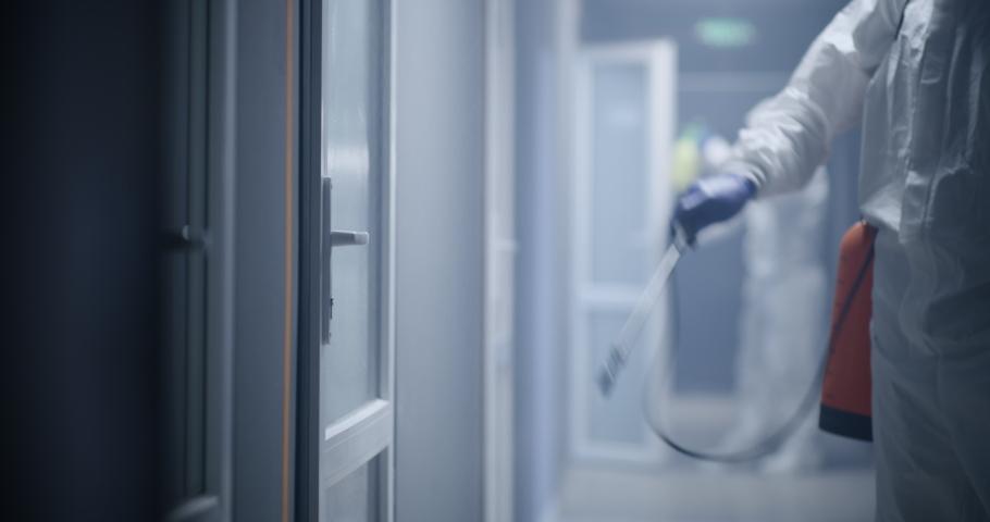 Medium shot of men in hazmat suits disinfecting doors. Shot was taken in 8K Royalty-Free Stock Footage #1052707799