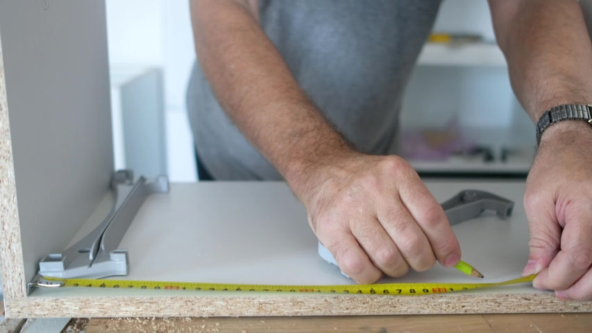 Carpenter marking laminate details with tape measure and pencil   Shutterstock HD Video #1052708054