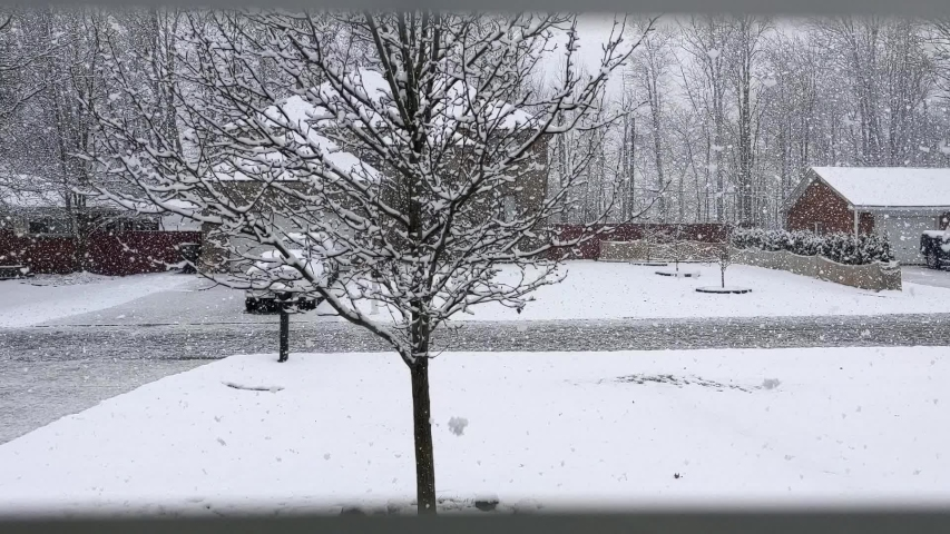 Slow motion of snowing from the house blinds view. It has the tree and can see neighbor house, mailbox, street, cars and forest.   Shutterstock HD Video #1052709278