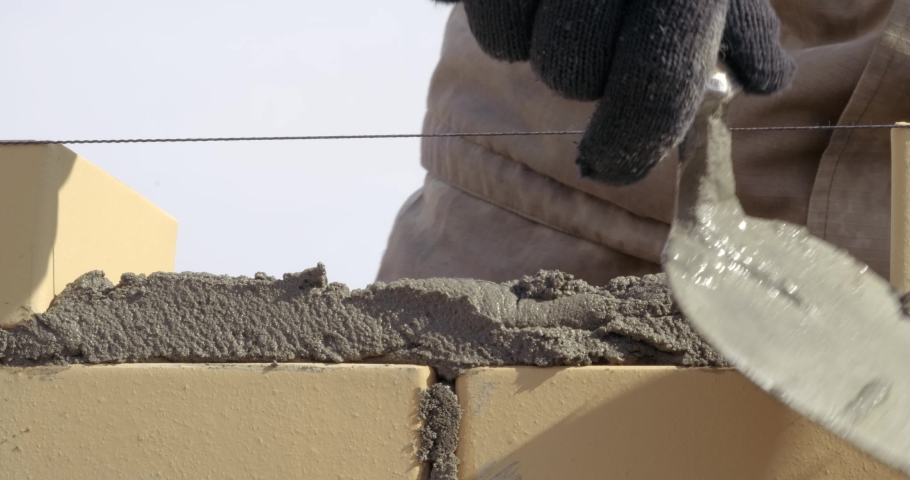 Bricklayer finishes brick row, fills last gap in brickwork, distributes mortar, takes out brick, stacks it, adjusts it with trowel according to level, removes excess mortar, construction site | Shutterstock HD Video #1052709722