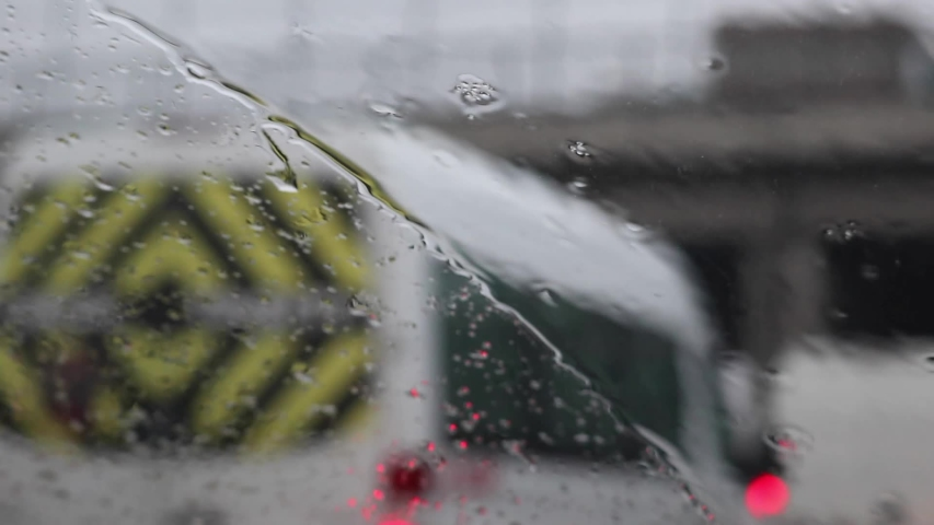 Rainy weather on the highway, rain drops on the windshield, moving wipers. Abstract cars, blurred backdrop. | Shutterstock HD Video #1052717837