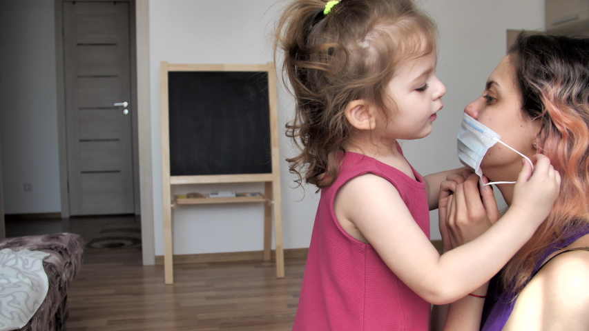 Little serious daughter puts on her mother medical mask. Stay home mom. Coronavirus or COVID-19. Cute little girl and mother in a protective mask at home. Mom teaches daughter to put on a medical mask | Shutterstock HD Video #1052718641
