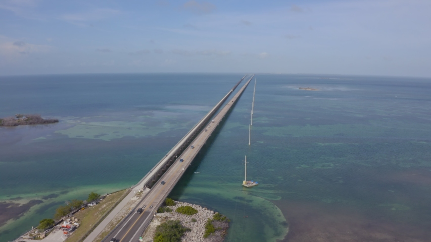 Aerial shot of the Seven Mile Bridge in Florida which connects several of the Florida Keys on the way to Key West. Drone flies above endless bridge over water