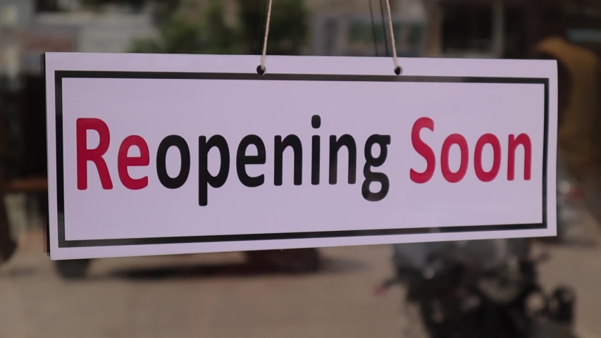 Reopening Soon Signage board in front of Businesses or Restaurant door after covid-19 or coronavirus outbreak - Concept of back to business after pandemic Royalty-Free Stock Footage #1052719694