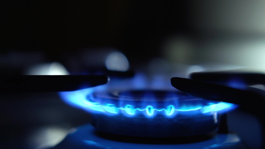 A man lights a gas stove with a match, close-up. Close up on the flame. Natural gas inflammation in stove burner. Gas burning from a kitchen gas stove | Shutterstock HD Video #1052721470