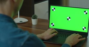 Male Video Editor Works on His Personal Computer with Green Screen Mock Up Display.