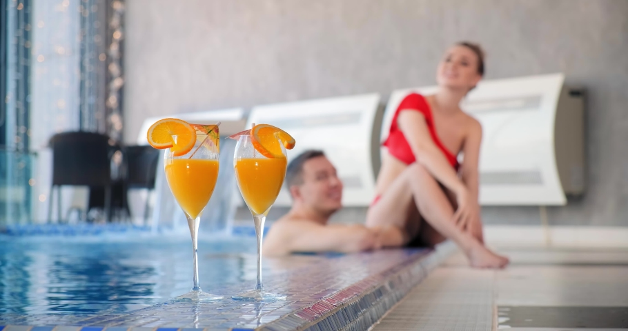 Blurry lady in bikini swimwear sits on pool edge talking to man swimming in water with cocktails on foreground   Shutterstock HD Video #1052723984