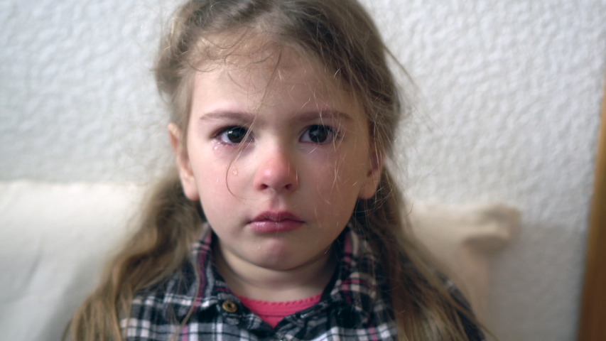 Crying child. Grumpy child. Little girls with tears on face. Difficult orphanage life.