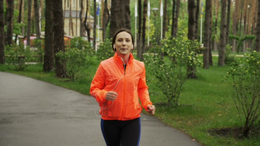 Brunette beautiful woman listening to music in earphones and jogging alone in empty city park. Happy sport woman in earphones is running in the park on rainy day. Female athlete training outdoors