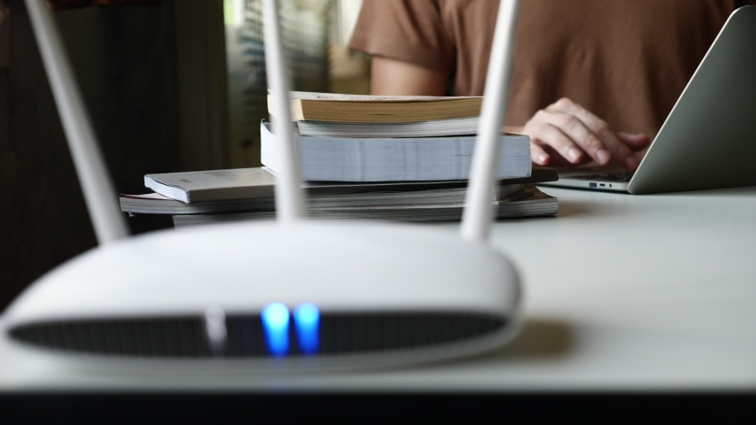 Close up of a wireless router and a man using laptop on the table Royalty-Free Stock Footage #1052728475