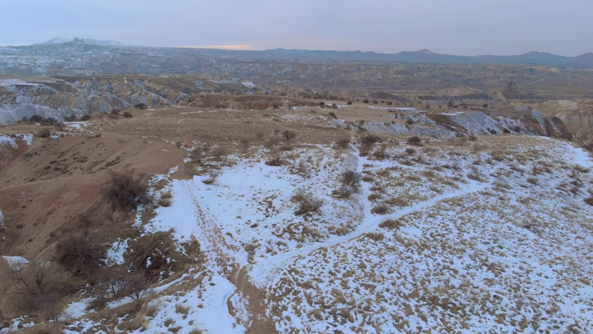 Aerial cinematic view of snow covered Red Valley with volcanic rock formations in Cappadocia, Turkey.   Shutterstock HD Video #1052730245