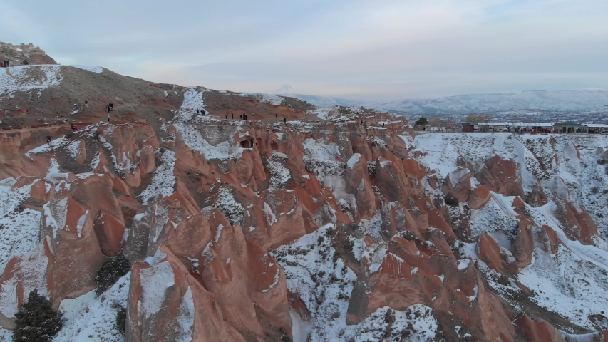 Aerial cinematic view of snow covered Red Valley with volcanic rock formations in Cappadocia, Turkey.   Shutterstock HD Video #1052730248
