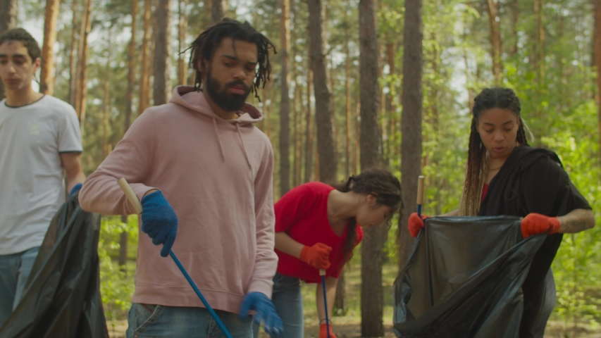 Group of diverse multiethnic eco-friendly young volunteers in protective gloves with garden tools picking up garbage and plastics into trash bags, caring for purity of nature during spring cleanup. | Shutterstock HD Video #1052730536