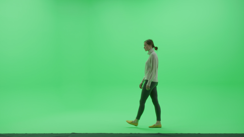 Green Screen Chroma Key Studio: Beautiful Young Woman Wearing Stylish Casual Clothes Walks Across Room Right to Left. Side View Camera Shot